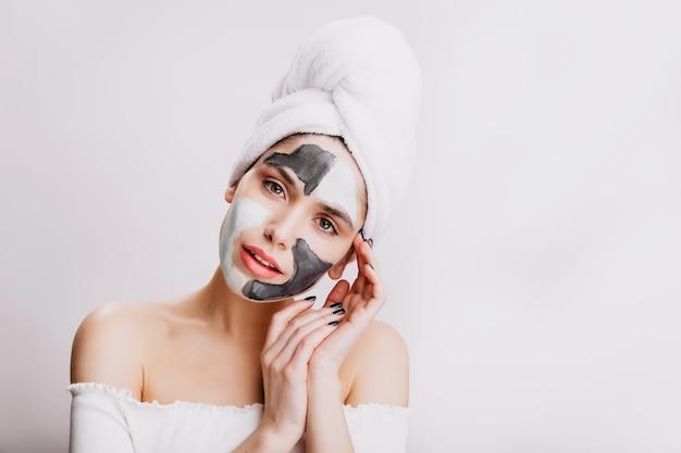 Close-up portret van aantrekkelijk meisje doet gezichtsmasker voor het slapen gaan. het volwassen vrouw stellen op witte muur.