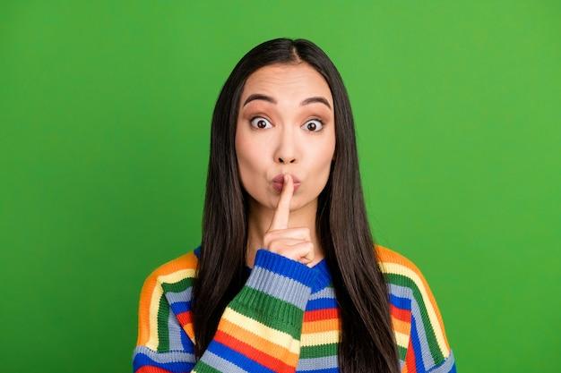 Close-up portret van aantrekkelijk mysterieus meisje met shh teken houd stilte geïsoleerd over heldergroene kleur achtergrond