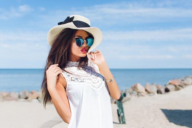 Close-up portret van aantrekkelijke brunette meisje met lang haar staande op het strand in de buurt van zee. ze raakt haar aan en kijkt ver weg.