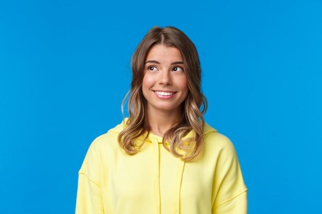 Close-up portret van aantrekkelijke europese blonde vrouw met kort haar, gele hoodie dragen, op zoek naar dromerige en domme linkerbovenhoek, glimlachend met witte stralende glimlach, permanent