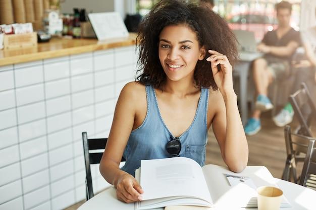 Close-up portret van aantrekkelijke jonge zwarte huid freelancer met golvend donker haar in modieus blauw shirt cmiling helder, in de camera kijken met ontspannen expressie, zittend in koffie sh