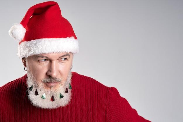 Close-up portret van aantrekkelijke man van middelbare leeftijd met versierde baard met kerstmuts en