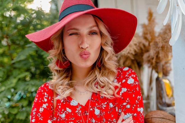 Close-up portret van aantrekkelijke stijlvolle blonde lachende vrouw in rode strooien hoed en blouse zomer mode outfit, grappig gezicht kus