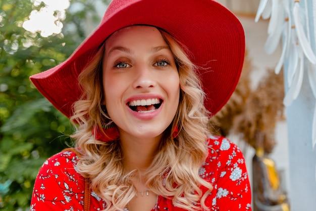 Close-up portret van aantrekkelijke stijlvolle blonde lachende vrouw in rode strooien hoed en blouse zomer mode outfit met glimlach