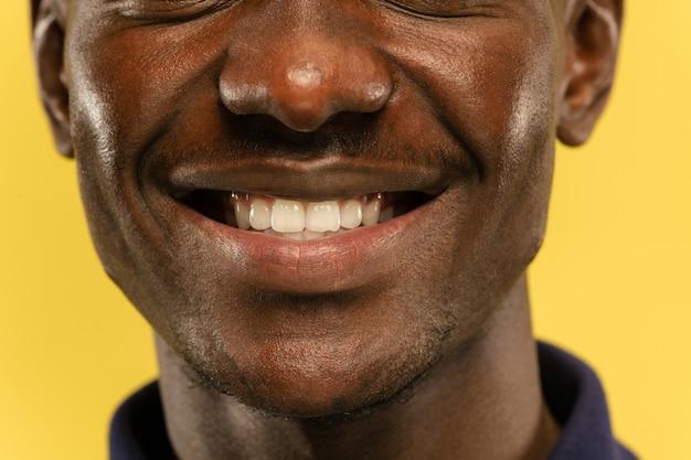 Close-up portret van afro-amerikaanse jonge man op gele studio achtergrond. mooi mannelijk model met verzorgde huid. concept van menselijke emoties, gezichtsuitdrukking, verkoop, advertentie. ziet er kalm en glimlachend uit.