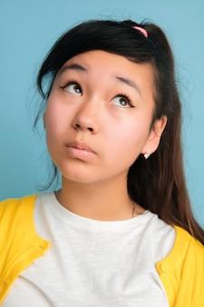 Close-up portret van aziatische tiener geïsoleerd op blauwe ruimte. mooi vrouwelijk donkerbruin model met lang haar
