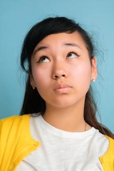 Close-up portret van aziatische tiener geïsoleerd op blauwe ruimte