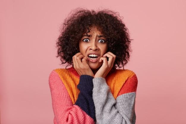 Close-up portret van bang hysterisch afrikaans amerikaans meisje met afro kapsel op zoek bang, in paniek, nerveus, bang, houdt vuisten dichtbij haar gezicht, geïsoleerd