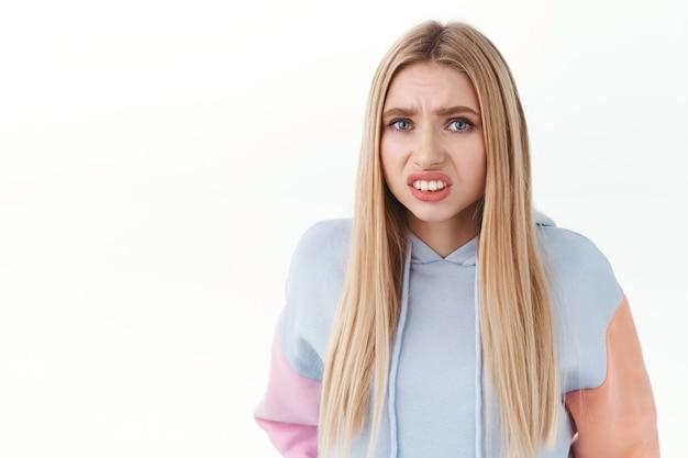 Close-up portret van beschaamd blond meisje, bukkend en gebalde vuisten, grimassend als starend naar iets cringy