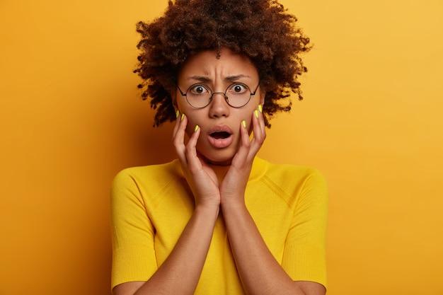 Close-up portret van beschaamde gekrulde jonge vrouw grijpt het gezicht, heeft een geschokte uitdrukking verbaasd, staart met afgeluisterde ogen, kan iets niet geloven, draagt een ronde bril en een t-shirt