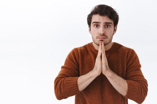 Close-up portret van bezorgde en verdrietige jonge knappe man die om hulp vraagt, smekend om hem te vergeven