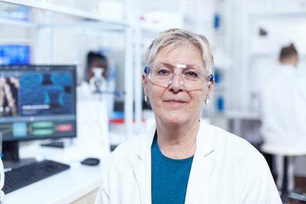 Close-up portret van bioloog kijken camera in steriel laboratorium. oudere wetenschapper met een laboratoriumjas die werkt aan de ontwikkeling van een nieuw medisch vaccin met een afrikaanse assistent op de achtergrond.