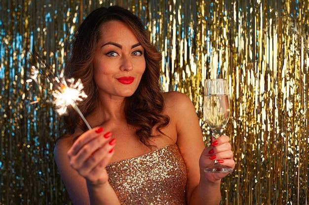 Close-up portret van blanke vrouw in gouden jurk jonge vrouw drinkt champagne en sparkler bedrijf op feestje op heldere gouden achtergrond, selectieve aandacht