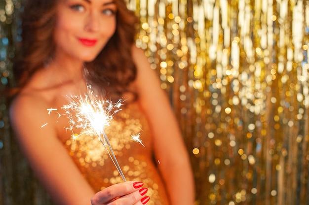 Close-up portret van blanke vrouw in gouden jurk met sterretje op feestje op heldere gouden achtergrond, selectieve aandacht