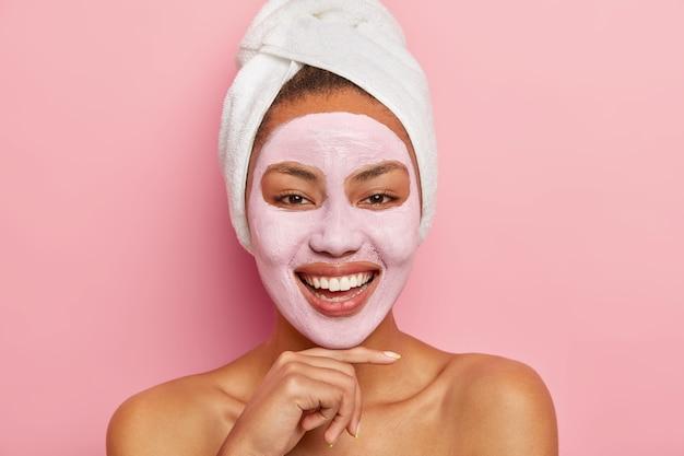 Close-up portret van blij positieve afro-vrouw raakt kin zachtjes, draagt een zachte handdoek, heeft een naakt lichaam met een gezonde huid, geïsoleerd over roze muur