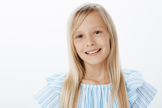 Close-up portret van blij schattig blond meisje in blauwe blouse, vrolijk lachend en starend, beleefd en vriendelijk terwijl de introductie aan nieuwe groep, staande