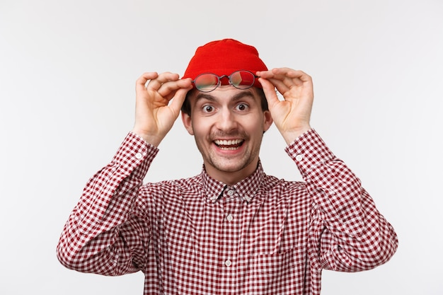 Close-up portret van blij vriendelijke verrast man bril opstijgen om hallo te zeggen, breed glimlachend geweldig ding zien, gevonden product en plukken, rode muts en geruit overhemd dragen, op een witte muur
