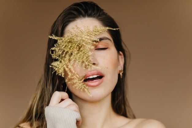 Close-up portret van blije europese vrouw met plant. het schitterende donkerbruine vrouwelijke model stellen op bruine muur met open mond.