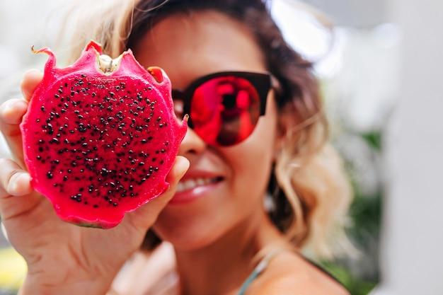 Close-up portret van blond meisje in heldere glazen poseren met pitaya. winnende blanke dame met exotisch fruit.