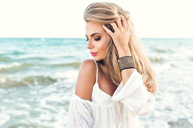Close-up portret van blond meisje met lang haar dromen op zee achtergrond. ze draagt witte kleren en versieringen bij de hand. ze kijkt naar beneden.