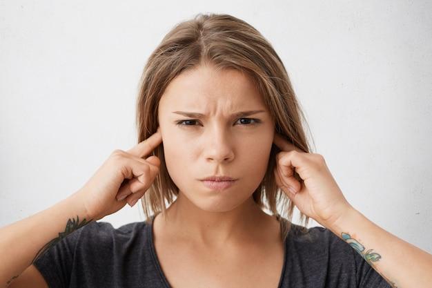 Close-up portret van boos geïrriteerd jong gemengd ras vrouwtje haar oren inpluggen om hard geluid van buren in appartement hierboven te vermijden, met geïrriteerde blik. negatieve menselijke emoties en reacties
