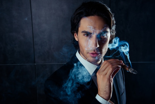 Close-up portret van brute knappe man met een sigaar met rook Premium Foto