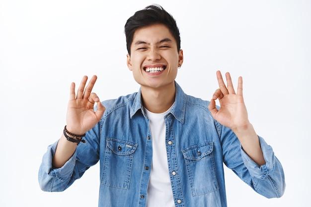 Close-up portret van charismatische, aantrekkelijke aziatische man garandeert de beste kwaliteit, beveelt product aan, lacht en glimlacht tevreden, assertief zal je het leuk vinden, witte muur.