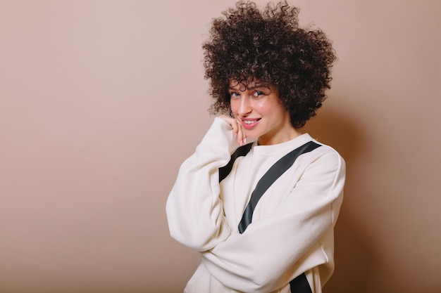 Close-up portret van charmante mooie vrouw gekleed witte trui heeft plezier en glimlacht op roze