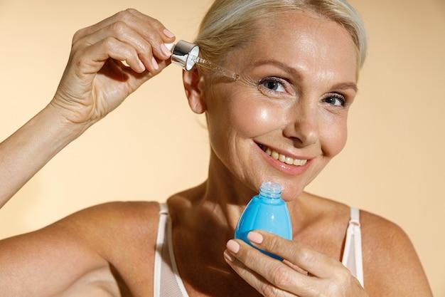Close-up portret van charmante rijpe blonde vrouw die lacht naar de camera terwijl ze zuur serum aanbrengt met