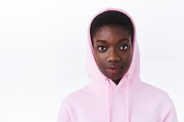 Close-up portret van cool aantrekkelijk hipster afrikaans-amerikaans meisje in roze hoodie, met kort kapsel