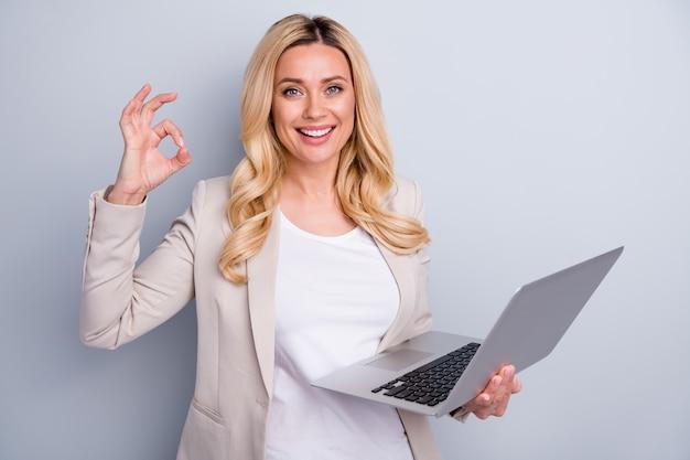 Close-up portret van dame financier houdt laptop met ok teken?