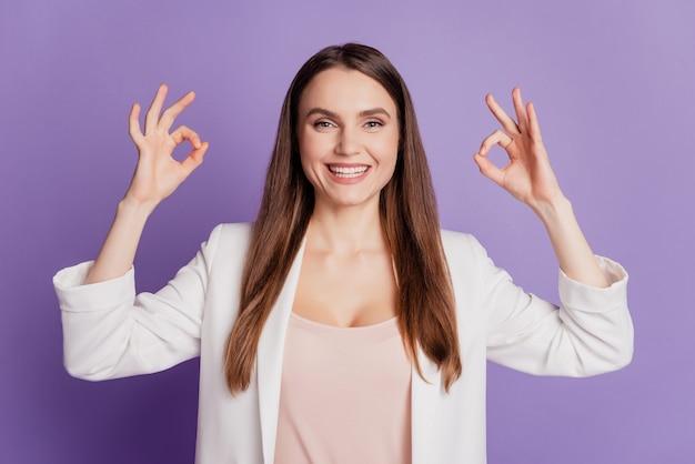 Close-up portret van dame met twee okey-tekens die een formeel pak op de paarse muur dragen