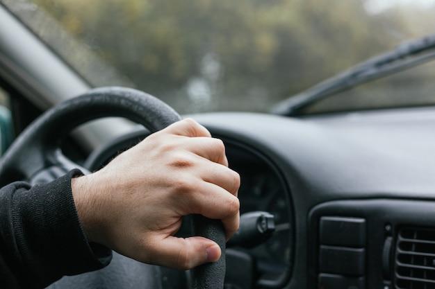 Close-up portret van de hand van een onherkenbare man die het stuur van een auto bestuurt tijdens een reis op een mistige en regenachtige winterdag