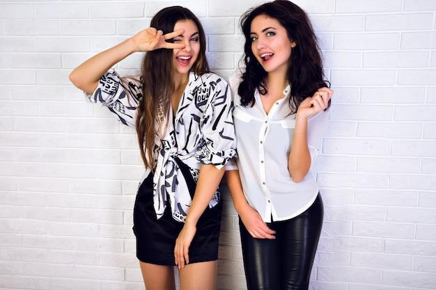 Close-up portret van de twee vriendinnen. meisjes gekleed in witte blouses en donkere billen. jonge meisjes met lichte make-up die bij de stad tegen een witte muur glimlachen.