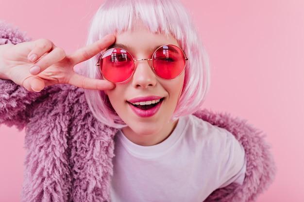 Close-up portret van debonair meisje in trendy peruke. binnen schot van lachende jonge vrouw in zonnebril geïsoleerd op roze muur