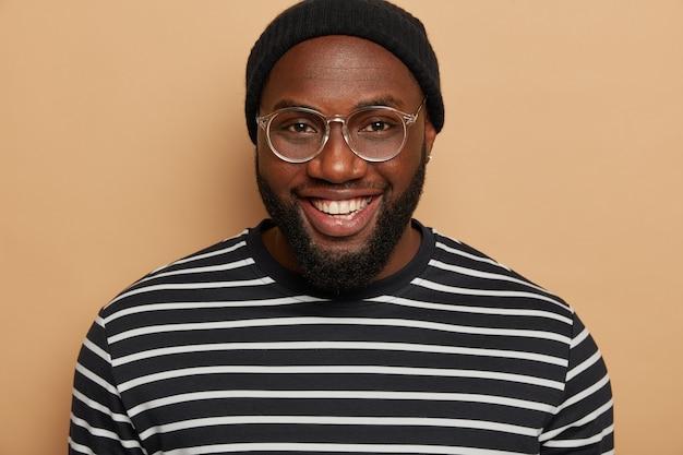Close-up portret van donkere huid volwassen man met dikke haren, glimlach toothy, draagt grote optische bril, gestreepte trui, blij vriend te ontmoeten