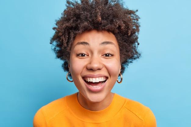 Close-up portret van donkere vrouw met natuurlijk krullend haar schone gezonde huid glimlacht in grote lijnen geluk heeft perfecte witte tanden draagt casual kleding geïsoleerd over blauwe muur.