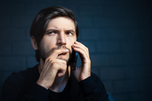Close-up portret van doordachte jongeman, praten over smartphone. achtergrond van zwarte bakstenen muur.