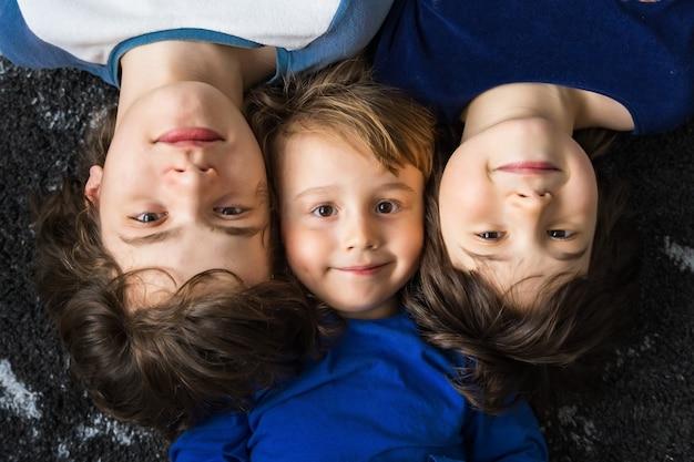 Close-up portret van drie broers van verschillende leeftijden, liggend op de vloer op een tapijt en kijkend naar de camera met een glimlach