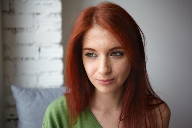 Close-up portret van dromerige aantrekkelijke jonge vrouw met mooie groene ogen, rood haar en sproeten mysterieus glimlachend, wegkijkend terwijl ze aan iets aangenaams denkend, binnenshuis poseren