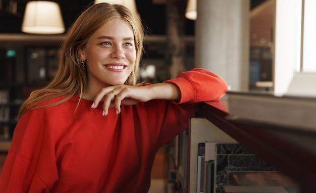 Close-up portret van dromerige slimme jonge vrouwelijke student met rood haar, leunend op een boekenplank in de bibliotheek.
