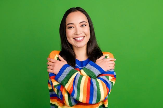 Close-up portret van een aantrekkelijk vrolijk meisje met een gestreepte pullover die zichzelf knuffelt geïsoleerd over een heldergroene kleurachtergrond
