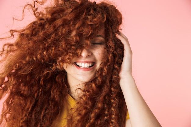 Close-up portret van een aantrekkelijke lachende gelukkige jonge vrouw met lang krullend rood haar staande geïsoleerd