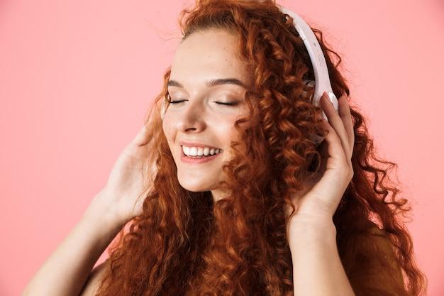 Close-up portret van een aantrekkelijke lachende jonge vrouw met lang krullend rood haar geïsoleerd staan, luisteren naar muziek met koptelefoon
