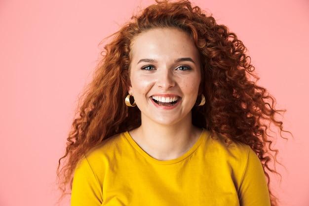 Close-up portret van een aantrekkelijke vrolijke jonge vrouw met lang krullend rood haar staande geïsoleerd
