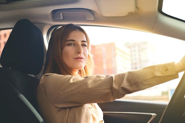 Close-up portret van een attente mooie jonge vrouw autorijden op een zonnige dag.