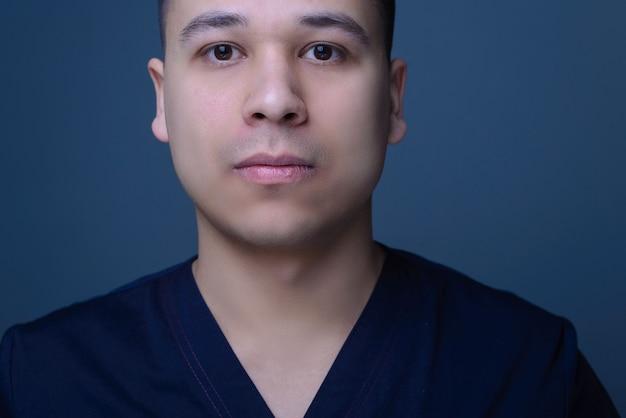 Close-up portret van een aziatische jonge dokter, chirurg, in een medisch pak