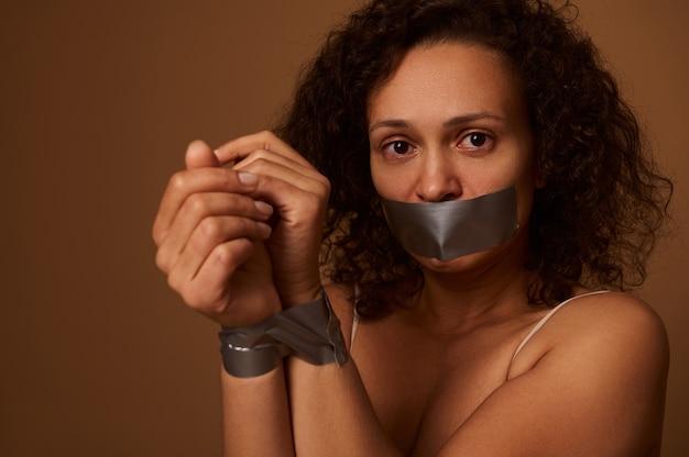Close-up portret van een bang halfnaakte gemengd ras vrouw met gebonden handen en gesloten mond, kijkend naar de camera, geïsoleerd op een gekleurde donkere achtergrond met kopie ruimte. eliminatie van geweld tegen vrouwen.