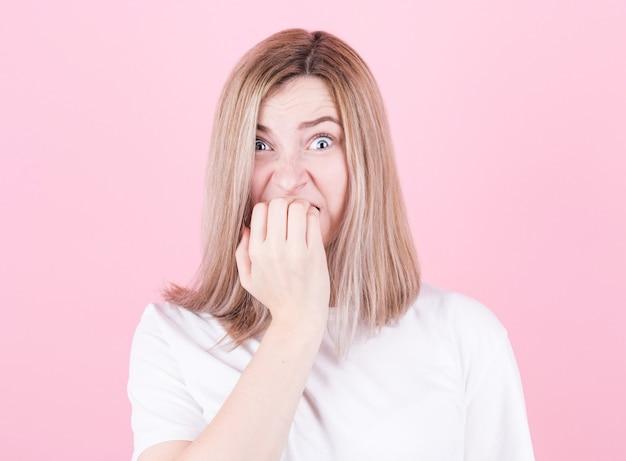 Close-up portret van een bezorgde tiener in wit t-shirt haar nagels bijten geïsoleerd over roze