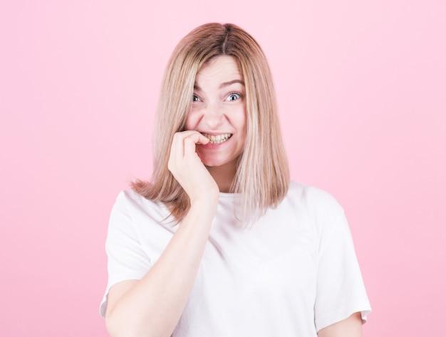 Close-up portret van een bezorgde tiener meisje in wit t-shirt haar nagels bijten geïsoleerd op roze